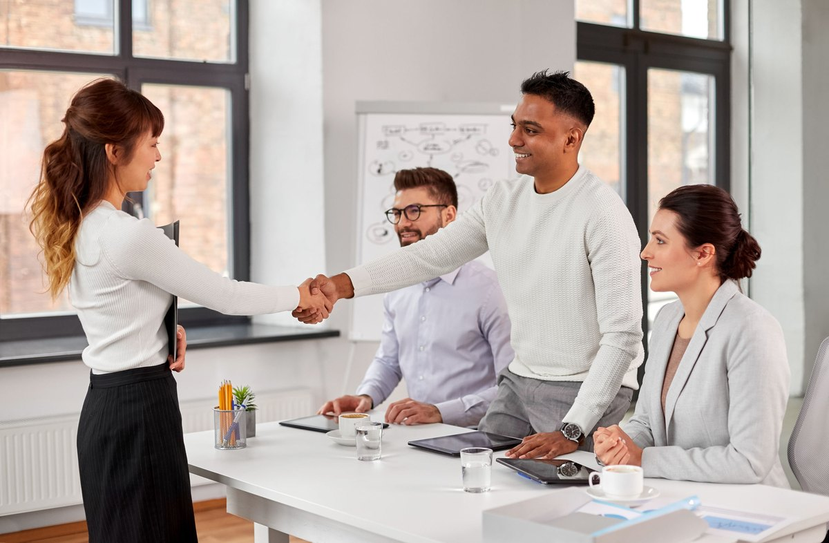 new job, hiring and employment concept - international team of recruiters having interview and shaking hands with asian female employee at office